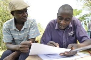 A field officer discusses loan repayment with a farmer in Chwele, Kenya.