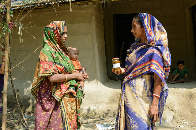 Field staff handing over a jar of fish chutney in Sunamgunj, Bangladesh. Photo by Finn Thilsted