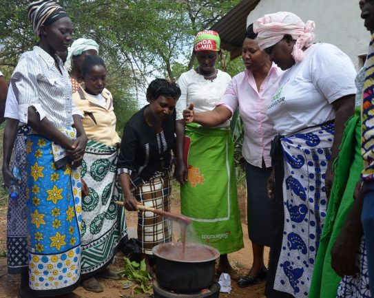 Rural Kenyan women learn a new way to cook finger millet porridge for better nutrition. Photo credit: Alina Paul-Bossuet
